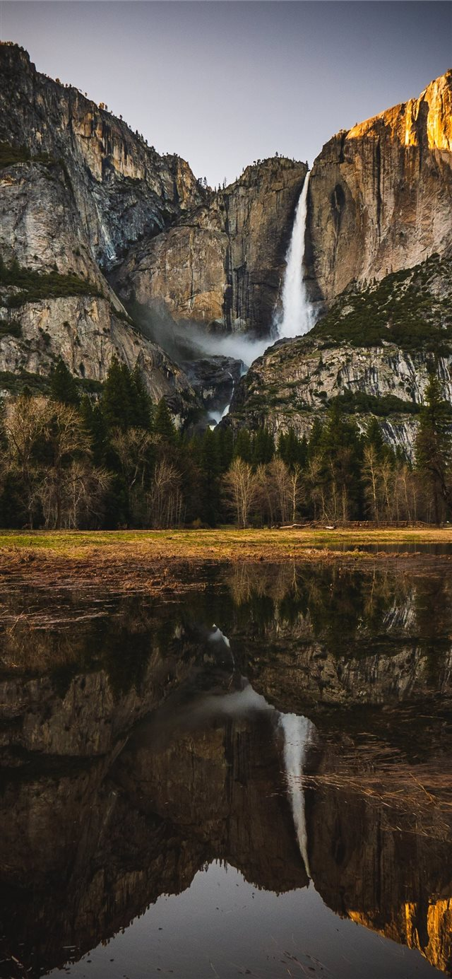 reflection of rock mountain and waterfalls on wate... iPhone X wallpaper