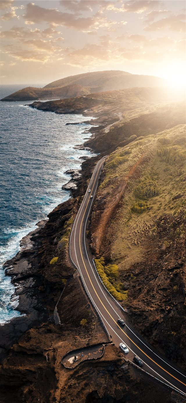 vehicles passing on road beside body of water duri... iPhone 11 wallpaper