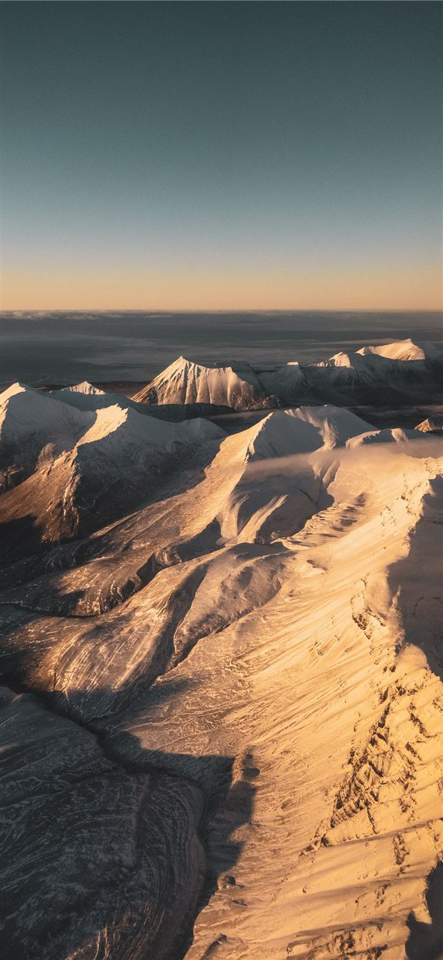brown and white mountains under blue sky during da... iPhone 11 wallpaper