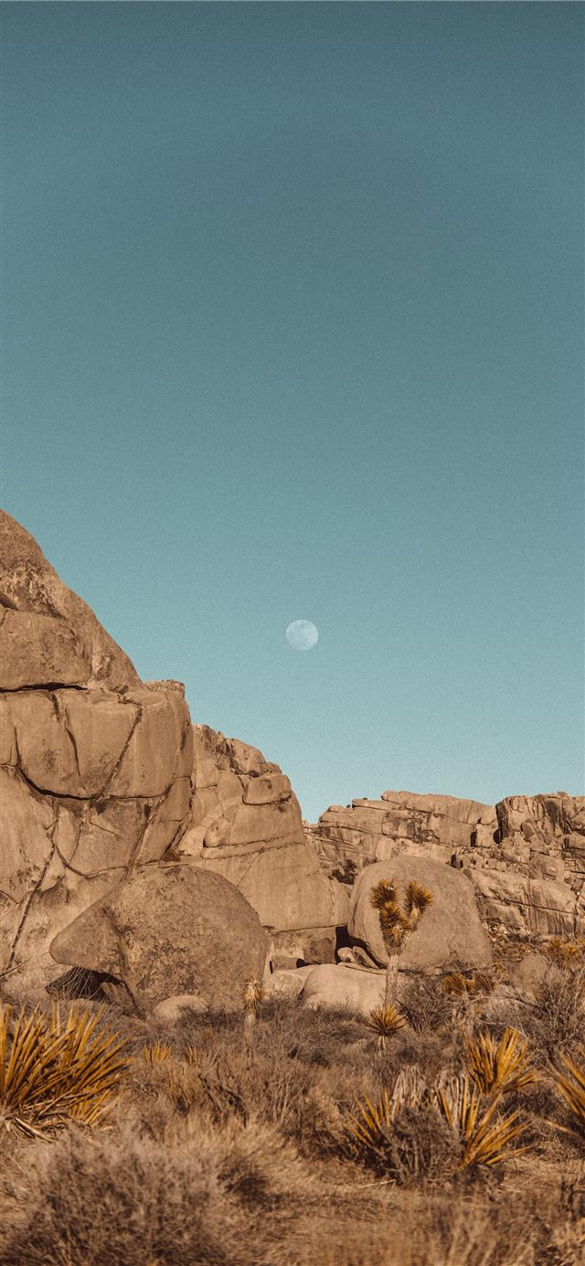 brown rock formation under blue sky during daytime iPhone 11 wallpaper