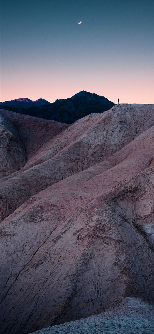 man standing on mountain during daytime iPhone X wallpaper