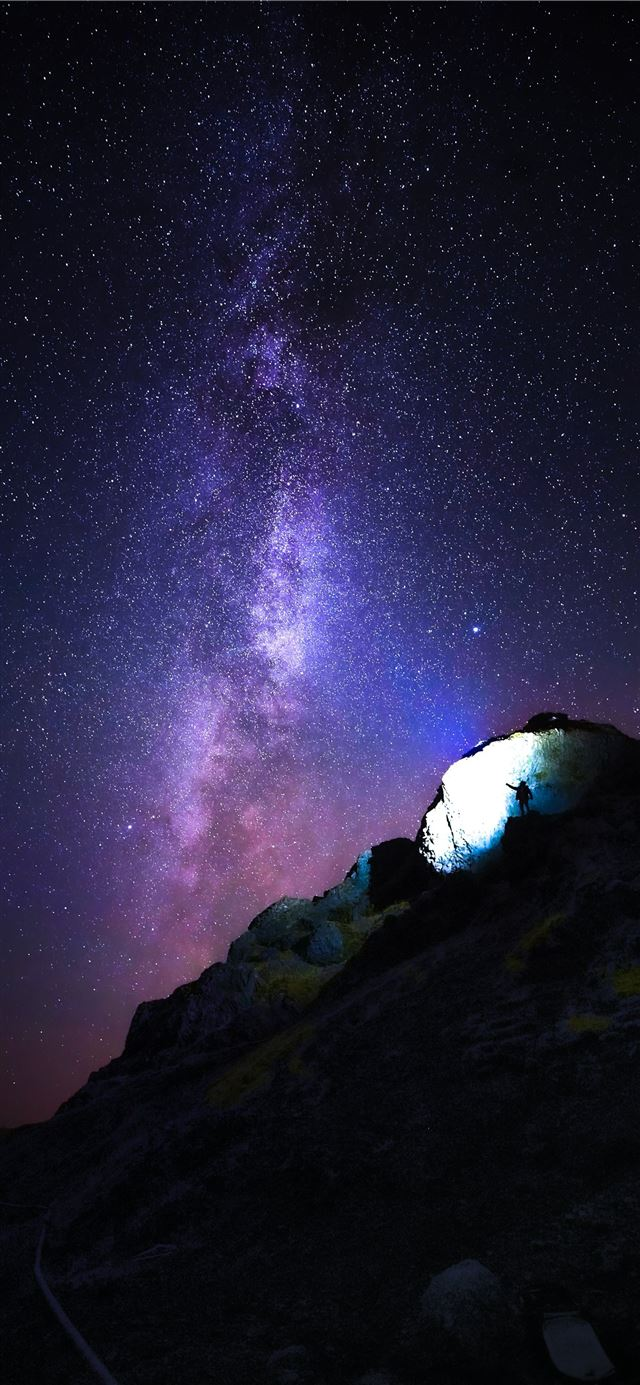 person standing on rock mountain under starry nigh... iPhone 11 wallpaper