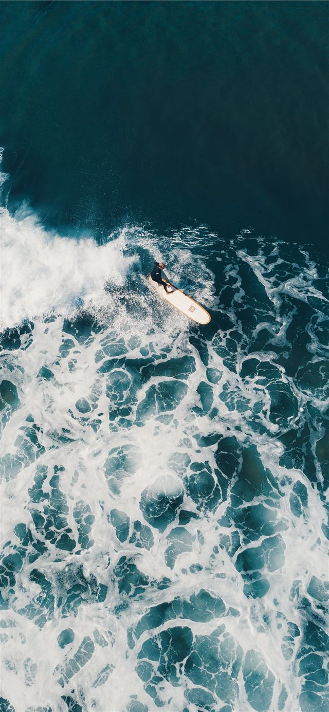 person surfing on sea waves during daytime iPhone X wallpaper