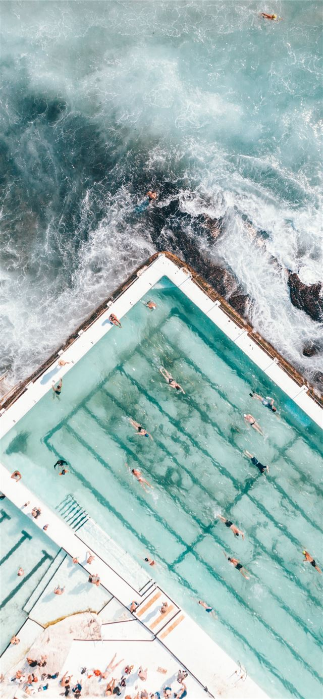 pool with people swimming nearby seashore iPhone 11 wallpaper