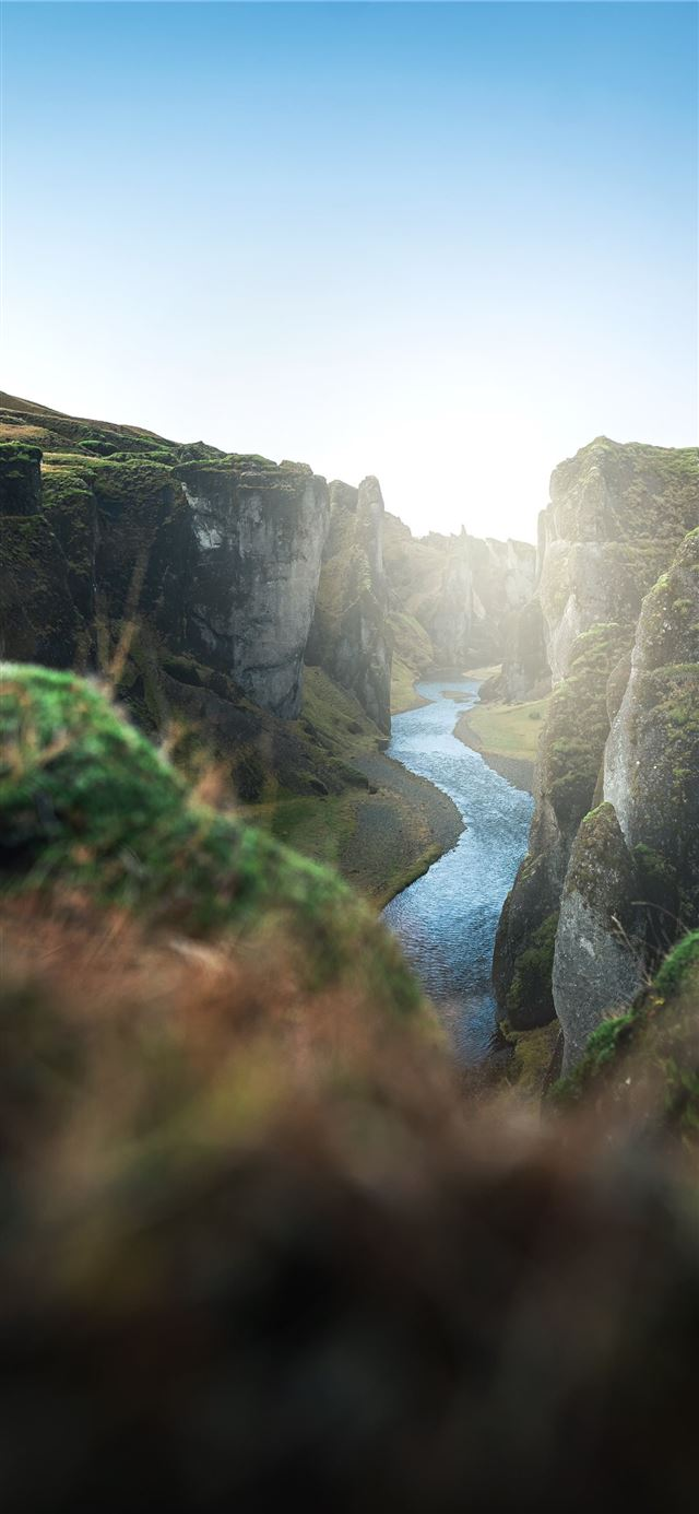river between green grass covered mountain during ... iPhone X wallpaper