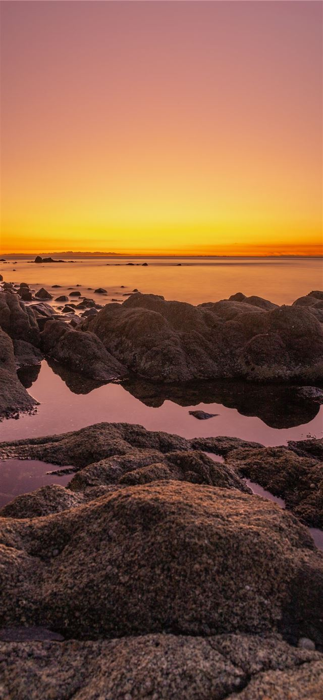 rocky shore during sunset with orange sky iPhone X wallpaper