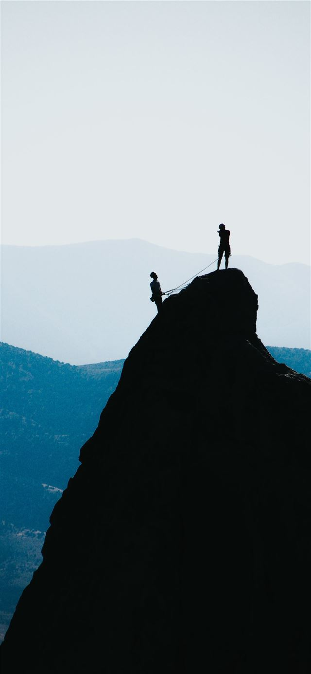 silhouette of two people standing on mountain duri... iPhone X wallpaper