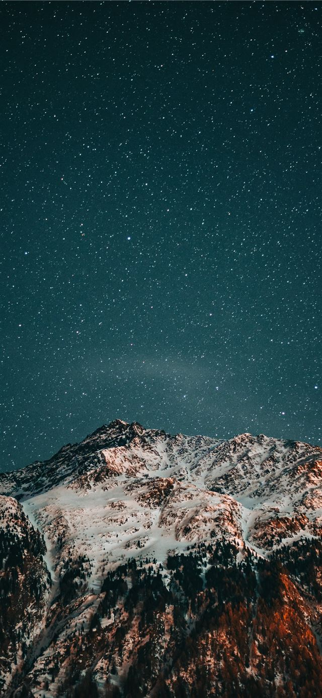 snow covered mountain under starry night iPhone X wallpaper