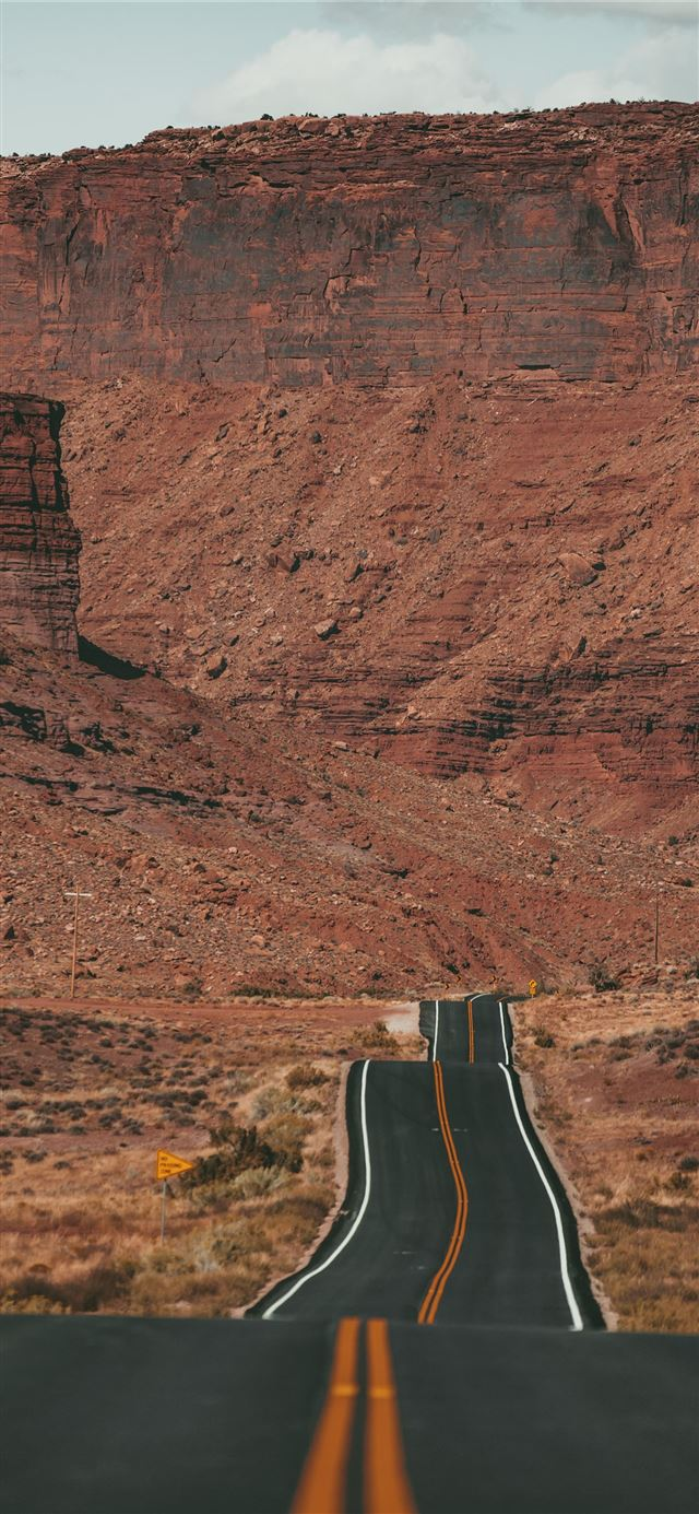 white car on road near brown rock formation during... iPhone 11 wallpaper