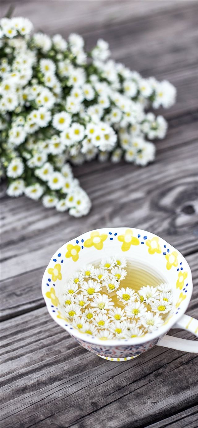 white and yellow cup with flowers on table iPhone X wallpaper